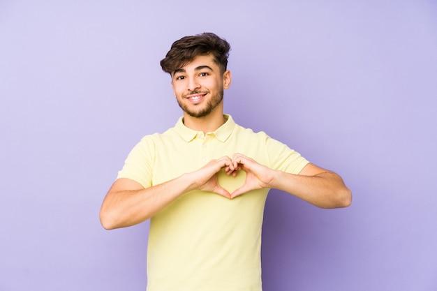 Jonge arabische man geïsoleerd op paars glimlachen en tonen een hartvorm met handen.