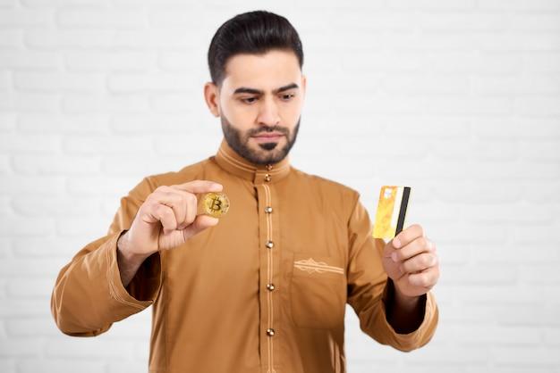Jonge arabische man houdt bitcoin en gouden creditcard