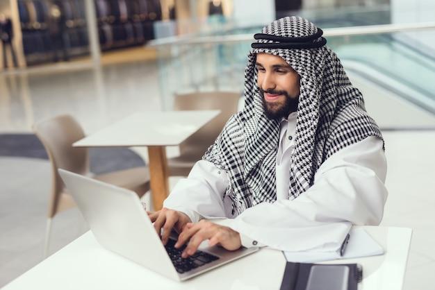 Jonge arabische man in sjaal met behulp van laptop in cafe.