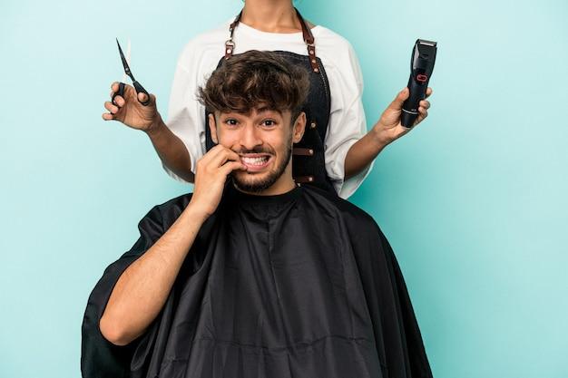 Jonge arabische man klaar om een kapsel te krijgen geïsoleerd op blauwe achtergrond bijtende vingernagels, nerveus en erg angstig.