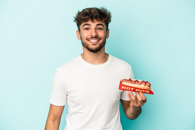 Jonge arabische man met een hotdog geïsoleerd op blauwe achtergrond gelukkig, glimlachend en vrolijk.