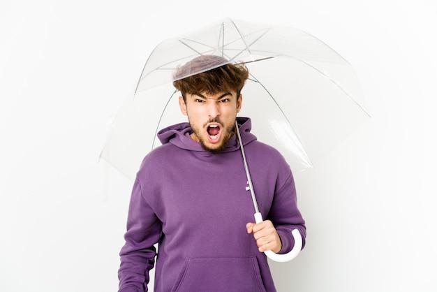 Jonge arabische man met een paraplu die erg boos en agressief schreeuwt.