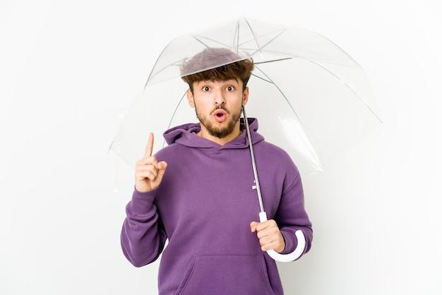 Jonge arabische man met een paraplu met een geweldig idee, concept van creativiteit.