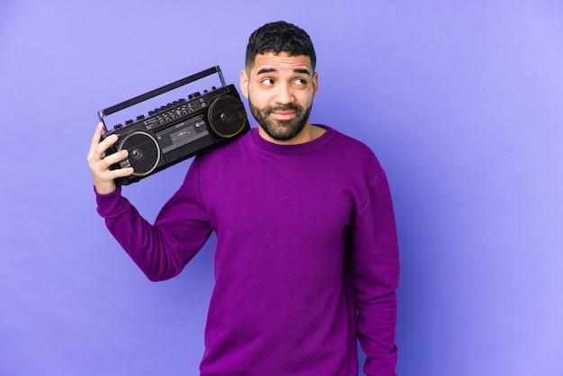 Jonge arabische man met een radio-cassette geïsoleerd jonge arabische man luisteren muziek droomt van het bereiken van doelen en doeleinden