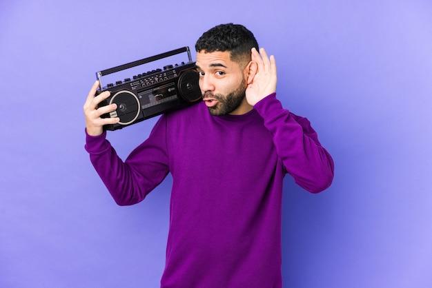 Jonge arabische man met een radio cassette geïsoleerd jonge arabische man luisteren muziek probeert te luisteren een roddel.