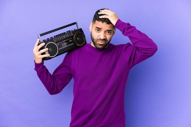 Jonge arabische man met een radio-cassette geïsoleerd jonge arabische man luisteren muziek wordt geschokt, ze heeft belangrijke bijeenkomst herinnerd.