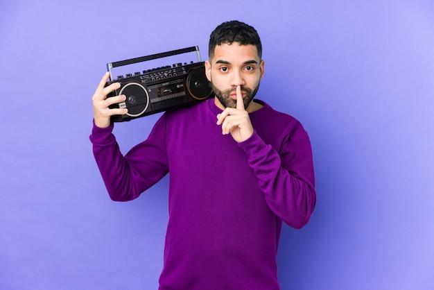 Jonge arabische man met een radiocassette geïsoleerd jonge arabische man luisteren muziek houden een geheim of vragen om stilte.