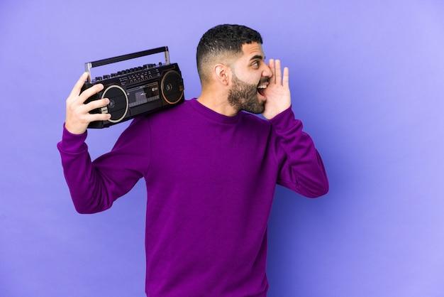Jonge arabische man met een radiocassette geïsoleerd jonge arabische man luisteren muziek schreeuwen en houden palm in de buurt van geopende mond.