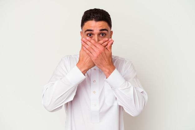 Jonge arabische man met typische arabische kleding geïsoleerd op een witte achtergrond geschokt die mond met handen bedekken.