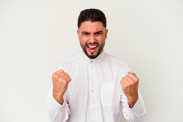 Jonge arabische man met typische arabische kleding geïsoleerd op een witte achtergrond, zorgeloos en opgewonden juichen. overwinning concept.