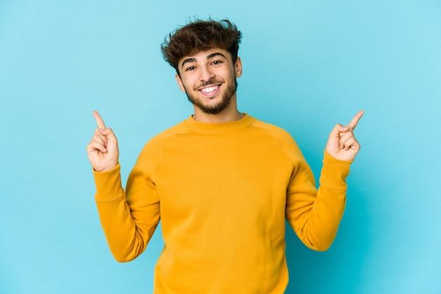 Jonge arabische man op blauw wijst naar verschillende kopie-ruimtes, kiest een van hen, toont met vinger.