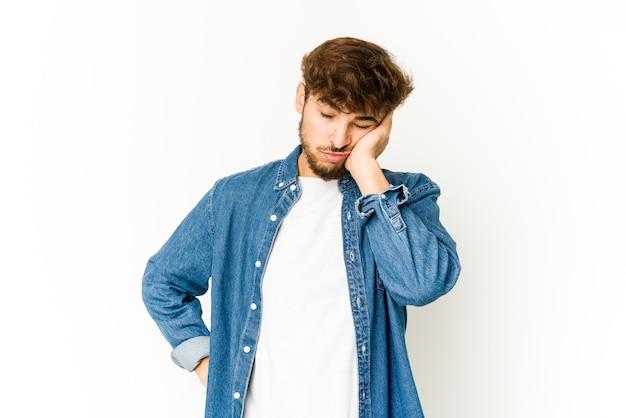 Jonge arabische man op een witte muur die zich verveelt, vermoeid is en een ontspannende dag nodig heeft.