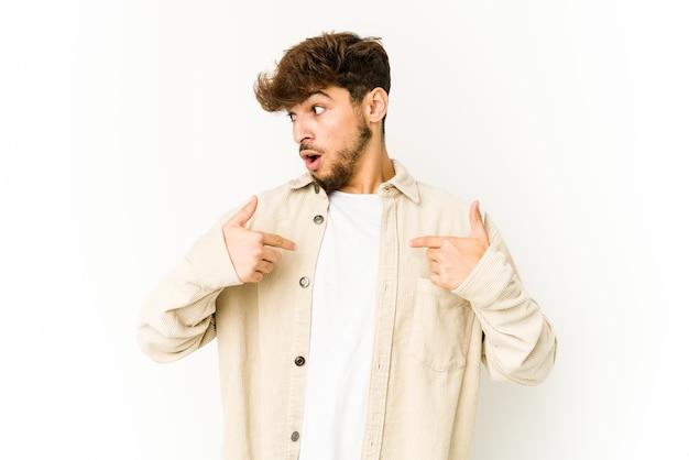 Jonge arabische man op witte achtergrond verrast wijzend met vinger, breed glimlachend.