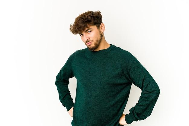 Jonge arabische man op witte muur fronsend gezicht in ongenoegen, houdt armen gevouwen