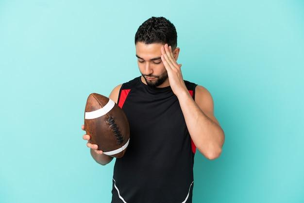 Jonge arabische man rugby spelen geïsoleerd op blauwe achtergrond met hoofdpijn