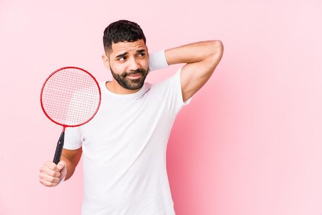 Jonge arabische man spelen badminton geïsoleerd aanraken achterkant van het hoofd, denken en het maken van een keuze.