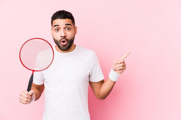 Jonge arabische man spelen badminton geïsoleerd wijzend naar de kant