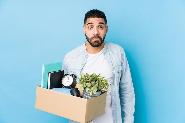 Jonge arabische man verhuizen naar een nieuw huis geïsoleerd haalt schouders en open ogen verward.