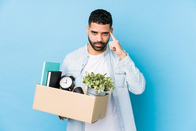 Jonge arabische man verhuizen naar een nieuw huis geïsoleerd wijzende tempel met vinger, denken, gericht op een taak.