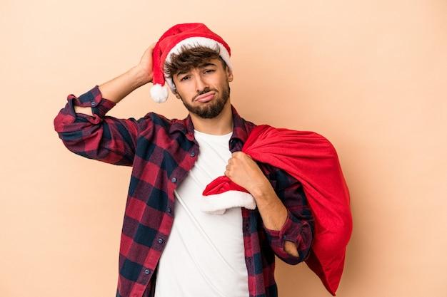 Jonge arabische man vermomd als de kerstman geïsoleerd op beige achtergrond geschokt, ze heeft een belangrijke ontmoeting onthouden.