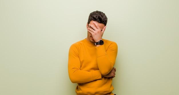 Jonge arabische mens die beklemtoond, beschaamd of verstoord, met hoofdpijn kijkt, die gezicht behandelt met hand tegen vlakke muur