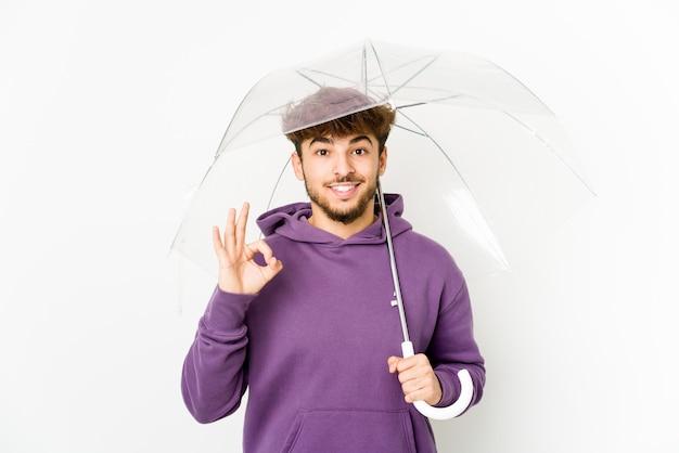 Jonge arabische mens die een paraplu vrolijk en zelfverzekerd houdt die ok gebaar toont.