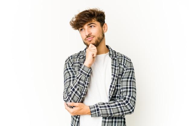 Jonge arabische mens die op witte muur zijwaarts kijkt met twijfelachtige en sceptische uitdrukking