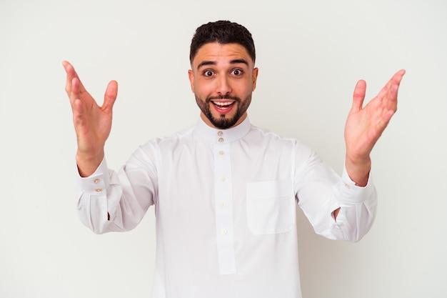 Jonge arabische mens die typische arabische kleding draagt die op witte achtergrond wordt geïsoleerd die een aangename verrassing ontvangt, opgewekt en handen opstelt.