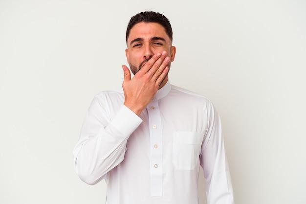 Jonge arabische mens die typische arabische kleding draagt die op witte achtergrond wordt geïsoleerd die geeuwt die een moe gebaar toont dat mond met hand behandelt.