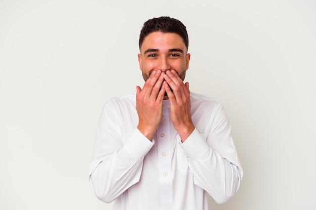 Jonge arabische mens die typische arabische kleding draagt die op witte achtergrond wordt geïsoleerd die over iets lacht, mond bedekt met handen.