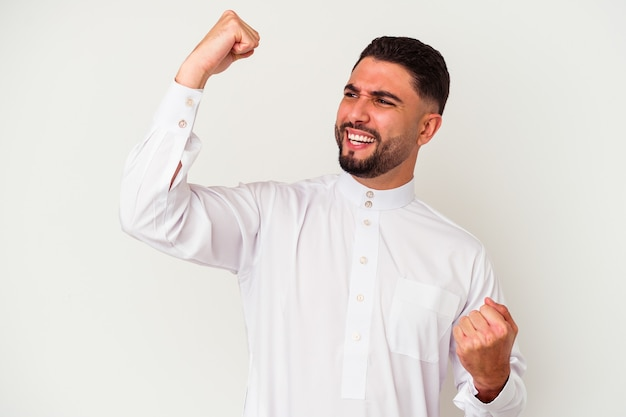 Jonge arabische mens die typische arabische kleding draagt die op witte achtergrond wordt geïsoleerd die vuist opheft na een overwinning, winnaarconcept.