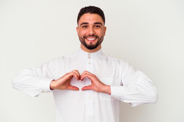Jonge arabische mens die typische arabische kleding draagt die op witte muur wordt geïsoleerd die en een hartvorm met handen glimlacht toont.