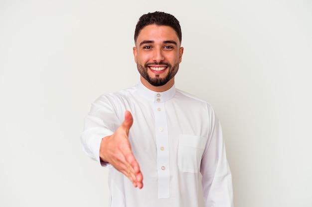 Jonge arabische mens die typische arabische kleding draagt die op witte muur wordt geïsoleerd die hand uitrekt bij camera in groetgebaar.