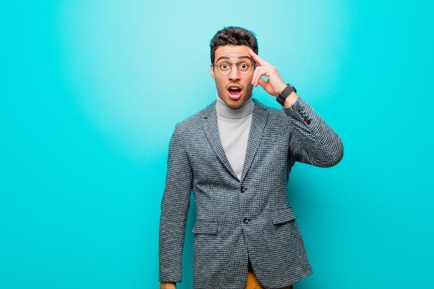 Jonge arabische mens die verrast, geschokt met open mond kijkt, die een nieuwe gedachte, een idee of een concept realiseert tegen blauwe muur