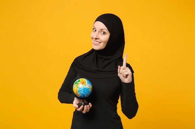 Jonge arabische moslim student meisje in hijab zwarte kleren houden in handen earth wereldbol geïsoleerd op gele muur portret. mensen religieuze levensstijl concept.