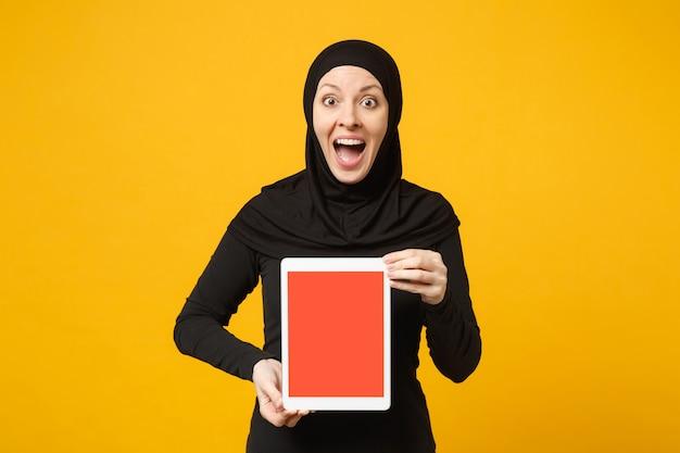 Jonge arabische moslim werknemer vrouw in hijab zwarte kleren houden en werken tablet pc-computer geïsoleerd op gele muur portret. mensen religieuze levensstijl concept.