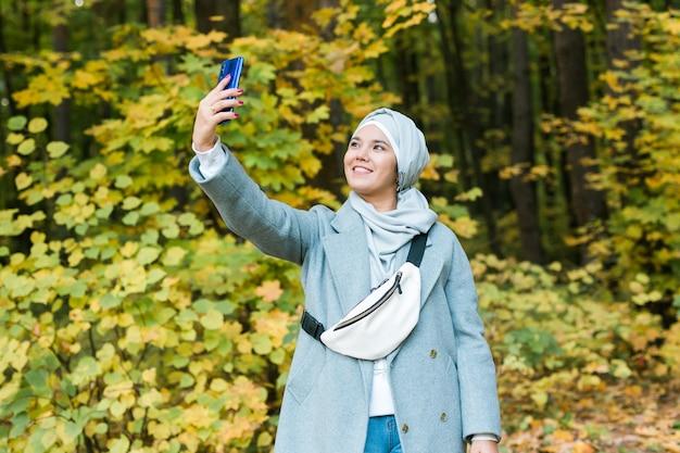Jonge arabische moslimvrouw in hijab-kleren die selfie op mobiele telefoon in park doen. mensen religieuze levensstijl concept. ruimte kopiëren.