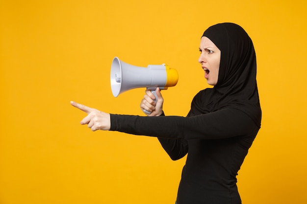Jonge arabische moslimvrouw in hijab zwarte kleding houdt in de hand megafoon omroepinstallatie geïsoleerd op gele muur portret. mensen religieuze levensstijl concept.