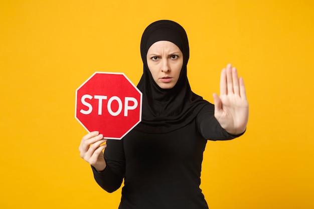 Jonge arabische moslimvrouw in hijab zwarte kleding houdt in handen rood bord met stoptitel geïsoleerd op geel muurportret. mensen religieuze levensstijl concept. .