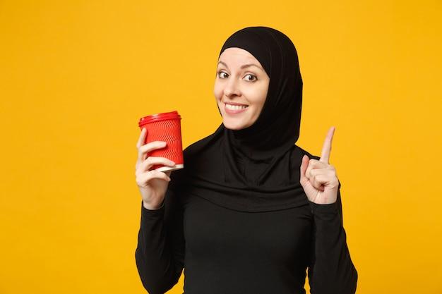Jonge arabische moslimvrouw in hijab zwarte kleding houdt papieren kopje koffie geïsoleerd op gele muur portret. mensen religieuze levensstijl concept.