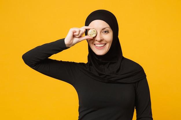 Jonge arabische moslimvrouw in hijab zwarte kleren houden in de hand met bitcoin munt valuta geïsoleerd op gele muur portret. mensen religieuze levensstijl concept.