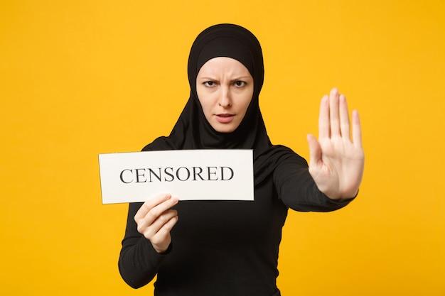 Jonge arabische moslimvrouw in hijab zwarte kleren houden in handen teken met gecensureerde titel geïsoleerd op gele muur portret. mensen religieuze levensstijl concept. .