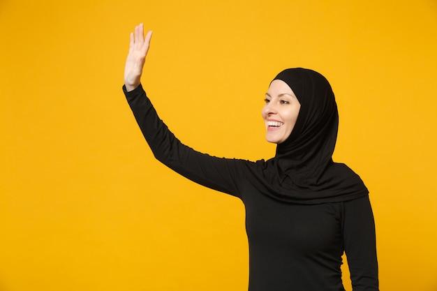 Jonge arabische moslimvrouw in hijab zwarte kleren zwaaien en begroeten met de hand als iemand merkt geïsoleerd op gele muur. mensen religieuze islam levensstijl concept.