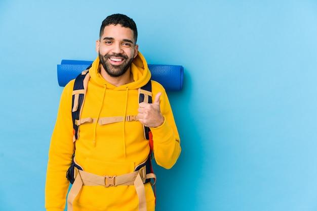Jonge arabische reiziger backpacker man geïsoleerd glimlachend en duim opheffen