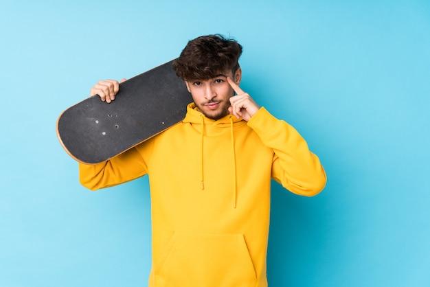 Jonge arabische skater man geïsoleerd wijzende tempel met vinger, denken, gericht op taak.