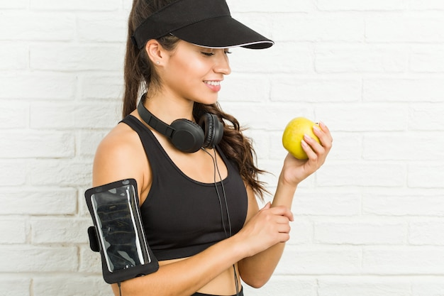 Jonge arabische sportieve vrouw die een appel houdt