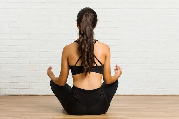 Jonge arabische sportieve vrouw het beoefenen van yoga op de vloer