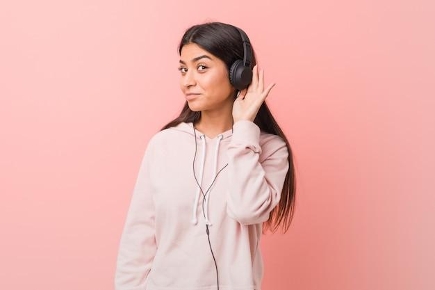 Jonge arabische vrouw die aan muziek luistert die aan een roddel probeert te luisteren.