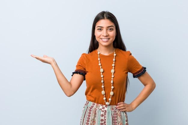 Jonge arabische vrouw die een exemplaarruimte op een palm toont en een andere hand op taille houdt.