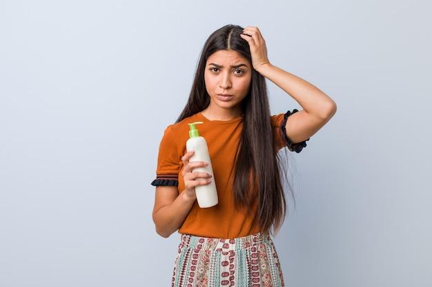 Jonge arabische vrouw die een fles crème vasthoudt die geschokt is, herinnert zich een belangrijke ontmoeting.